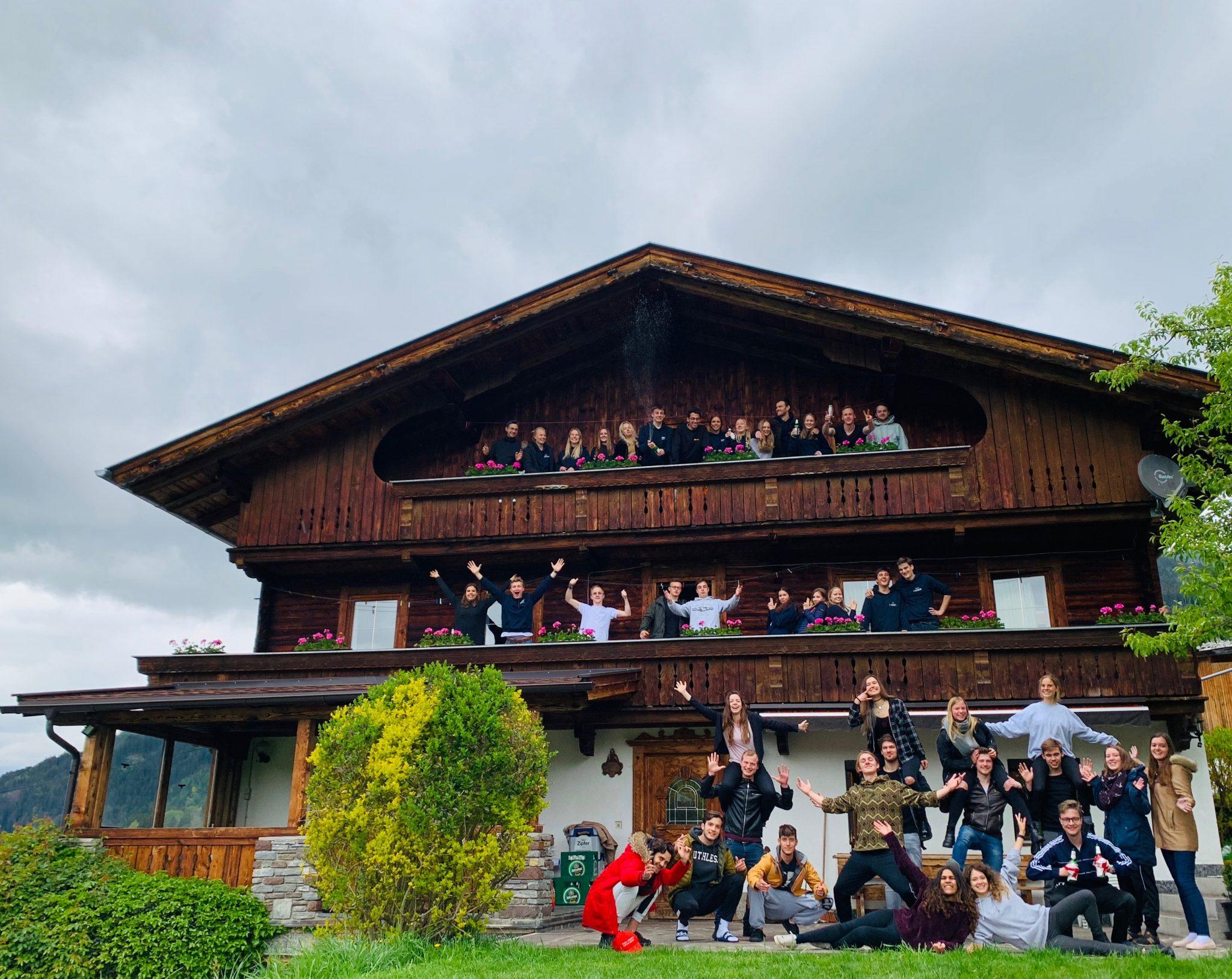 Berghütte mit Balkon, Studenten stehen auf Balkon und im Garten vor der Hütte